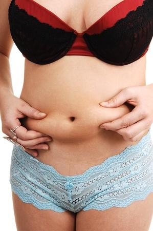 culotte fille: Une jeune femme debout dans la culotte bleu et noir soutien-gorge et la v�rification de la graisse sur son ventre, pour fond blanc. Banque d'images