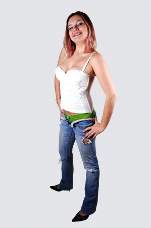 A young woman in jeans, green panties and a white corset, standing in heels and smiling into the camera on light gray background.