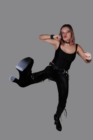 A young punk woman in black leather pants and a black corset and boots, standing for gray background an kicking with her leg. photo