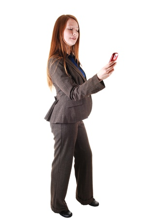 A business woman in a brown suit standing in profile in the studio, with her long red hair and dialing on her cell phone for white background. photo