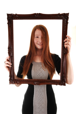 An young woman with long red hair holding a picture frame, in a black dress, with her hair over one eye, on white background. photo