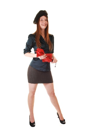 A young pretty woman with long red hair in a green blouse and brown  skirt wearing a hat with buttons on and a red umbrella, for white background.  photo