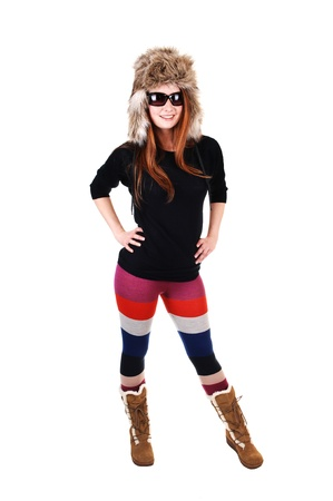 A pretty woman with long red hair in colorful tights, a black sweater  and a fur hat and brown boots smiling for a portrait for white background. 版權商用圖片