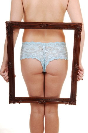 nice butt: A young woman in blue panties, holding a picture frame on the back, showing her nice butt, for white background. Stock Photo
