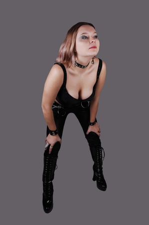A young punk woman in black leather pants, black corset and boots and a hat, bending forward, standing for gray background. photo