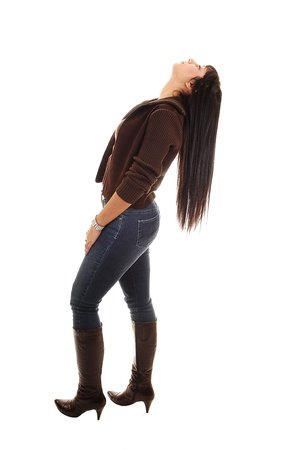 A pretty woman in jeans and boots and long black hair bending her head back, her hair can fall down, on white background.