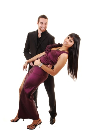 A young couple in a long burgundy dress and he in a black suit dancing in the studio over white background.