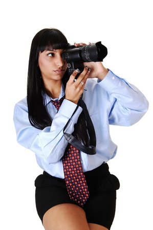An pretty young woman with a dELS camera taking some pictures, in black shorts and a blue shirt and tie, sitting, over white background. photo