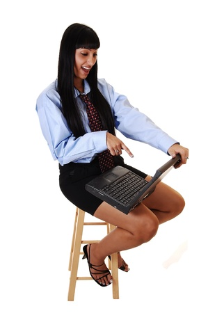 A pretty woman sitting on a chair and a laptop on her lap found something funny on her computer, in shorts and a blue shirt and tie, over white. photo