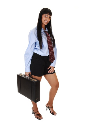 A pretty business woman in shorts, blue shirt and tie standing with a  briefcase in her hand, smiling into the camera, on white background.