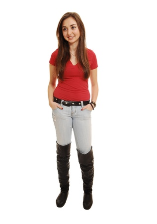 A pretty teenager standing in the studio in long boots and jeans, smiling with her long brunette hair, on white background. Imagens