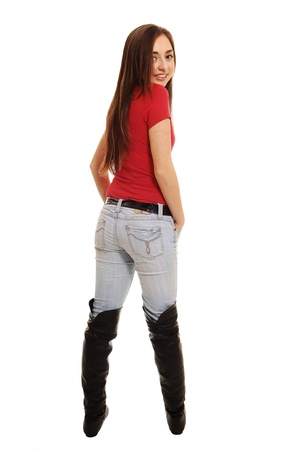 over shoulders: A pretty teenager standing in the studio in long boots and jeans, from the back with her long brunette hair, on white background. Stock Photo