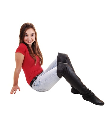 sixteen: A beautiful young girl sitting on the floor in long boots and jeans and a red sweater, with her long brunette hair, over white. Stock Photo