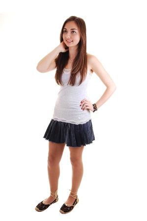 白い背景の上に短いスカートと灰色の t シャツ、彼女長いブルネットの髪を立っている美しい 10 代。