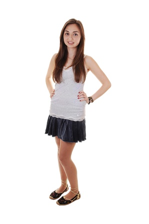 long skirt: An beautiful teenager standing in a short skirt and gray t-shirt, with her long brunette hair, over white background.