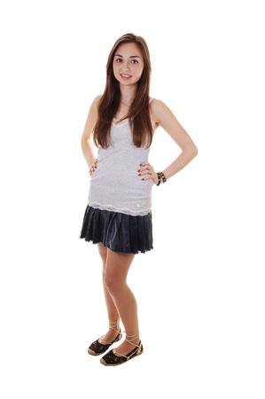 falda corta: Una hermosa adolescente pie en una falda corta y una camiseta gris, con el pelo largo Morena, sobre fondo blanco.