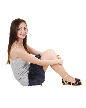 An beautiful teenager sitting on the floor in a short skirt and gray t-shirt,  with her long brunette hair, over white background.