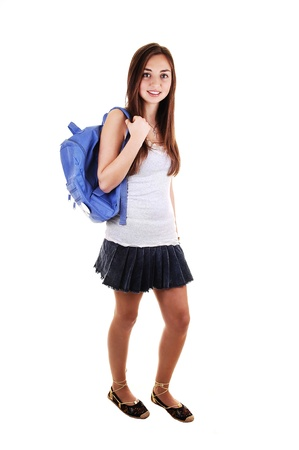A pretty teenager in a short skirt and a blue backpack over her shoulder standing in the studio for white background. Stock Photo - 8567477
