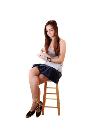 study: A young teenager sitting on a chair, in a skirt and with long brunette hair and a notebook in her hand, for white background. Stock Photo