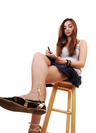 long: A young teenager sitting on a chair, in a skirt and with long brunette hair and a notebook in her hand, for white background. Stock Photo