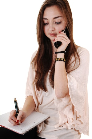 A pretty teenager talking on a cell phone with a notebook on her lap with lovely long brunette hair for white background. photo
