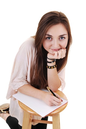 A beautiful teenager kneeling for a chair and writing in her  notebook, smiling into the camera, for white background. photo