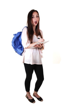 An surprised teenager with a blue backpack over her shoulder in an beige blouse and black tights, with a notebook in her hand, over white. Stock Photo - 8567473