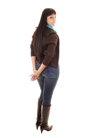 brown: A beautiful woman standing with her back to the camera in jeans and a brown sweater and boots and long black hair, on white background.