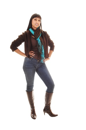 brown: A beautiful woman standing with her front to the camera in jeans and a brown sweater and boots and long black hair, on white background. Stock Photo