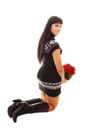 A pretty woman in a short brown dress and boots kneeling on the floor with red roses, smiling into the camera, over white.