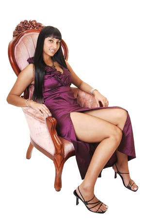 A gorgeous woman sitting in a antic pink armchair in a long burgundy evening dress and her long black hair falls over her shoulder, on white. photo