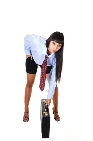 A pretty business woman in shorts, blue shirt and tie bending down to  her briefcase, smiling into the camera, on white background.