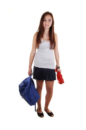 A pretty teenager in a short skirt and a blue backpack in her hand and an folded umbrella, standing in the studio for white background. 版權商用圖片