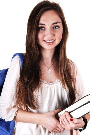 A pretty teenager in a beige blouse and a blue backpack over her shoulder and books in her hand, standing in the studio for white background. photo