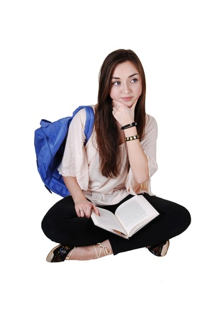 An teenager sitting on the floor with a blue backpack over her shoulder in a blouse and black tights, with a book on her lap, for white background. photo
