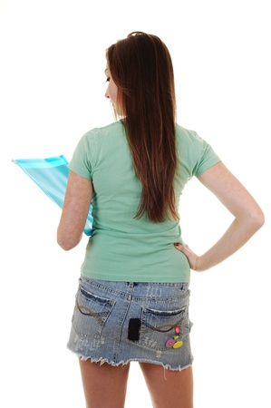 A pretty teenager in a green T-shirt and a blue short skirt, with long  brunette hair, standing from the back in the studio for white background. photo