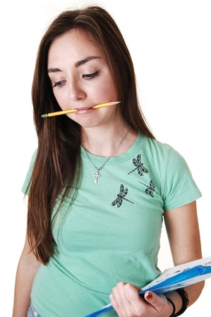 A pretty teenager in a green T-shirt and a pencil in her mouth, with long  brunette hair, standing in the studio for white background. photo