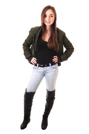 long: A beautiful teenager girl in a green winter jacket and long black boots and long brunette hair smiling into the camera.