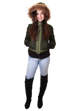 A beautiful teenager girl in a green winter jacket with an fur hood and  long brunette hair smiling into the camera. photo