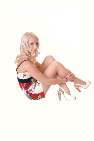 A teenager sitting on the floor in a colorful dress in the studio, with her long blond hair, for white background. Stock Photo - 8736328