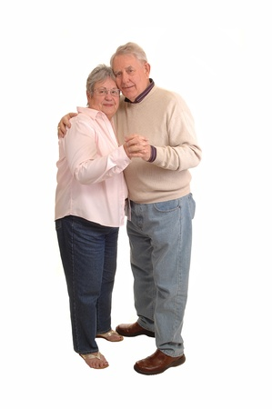 A couple of seniors in the sixties dancing in the studio, for white background.