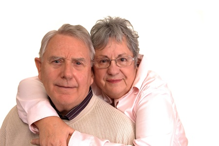 A senior couple in a closeup shot hugging for a portrait, on white background. photo