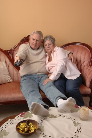 An senior couple sitting on the sofa in there living room and switching channels on the TV, for white background. photo