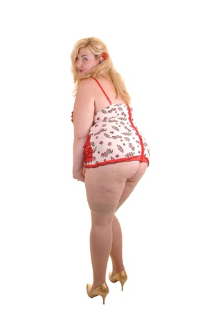 An big overweight woman standing from the back in beige lingerie and  stockings in the studio, for white background.