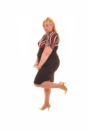 An big heavy woman standing in a black dress and on one leg in the  studio, for white background.