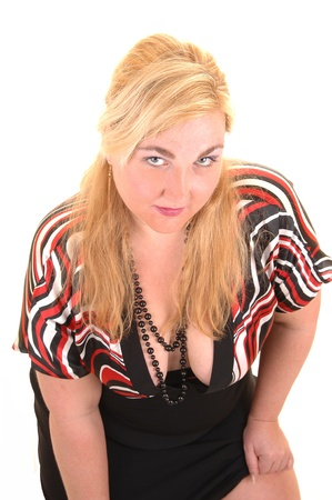 An closeup portrait of a heavy woman with blond hair, in an black dress, looking into the camera for white background. photo
