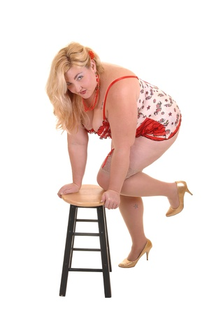 An big overweight woman standing in beige lingerie and stockings in the studio, kneeling with one leg on a chair, for white background. Stock fotó