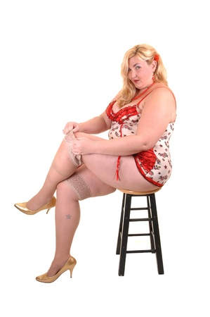 plus size woman: An big overweight woman in beige lingerie putting her stockings  on and sitting on a chair the studio, for white background. Stock Photo