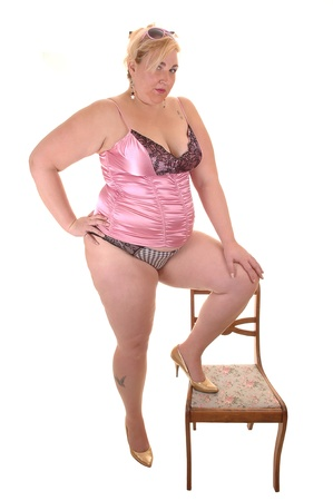 An big overweight woman in pink lingerie standing, with one leg on a  chair, in the studio, for white background. Stock Photo