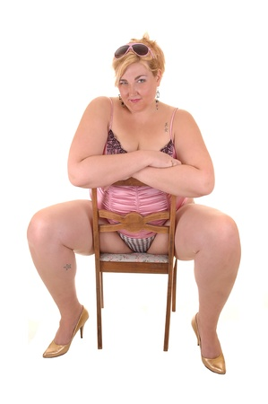 An big overweight woman in pink lingerie sitting backworts on a chair in the studio, for white background. Stock Photo